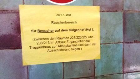 """Ein vergilbtes Schild aus Papier, das an einer Wand hängt und die Aufschrift trägt: """"Ab 1.1.2008 - Raucherbereicht - für Besucher auf dem Galgenhof Hof L"""" und darunter einer genaueren Beschreibung, wie man dorthin gelangt."""