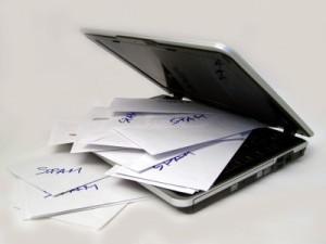 """Halb aufgeklappter Laptop. Auf der Tastatur und davor liegen zahlreiche weiße Zettel, auf denen handschriftlich jeweils einmal das Wort """"SPAM"""" geschrieben steht. Das Bild symbolisiert den Missbrauch der Kommentarfunktion von Blogs für Spam."""