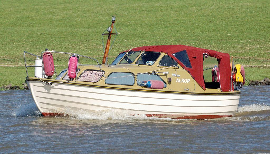 """Ein Boot in Verdränger-Bauweise mit der Beschriftung """"Alkor"""" in Fahrt auf einem Fluss."""