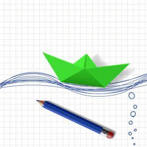 Ein Symbolbild für den Bootskauf mit einem grünen aus Papier gefalteten Boot und einem Bleistift